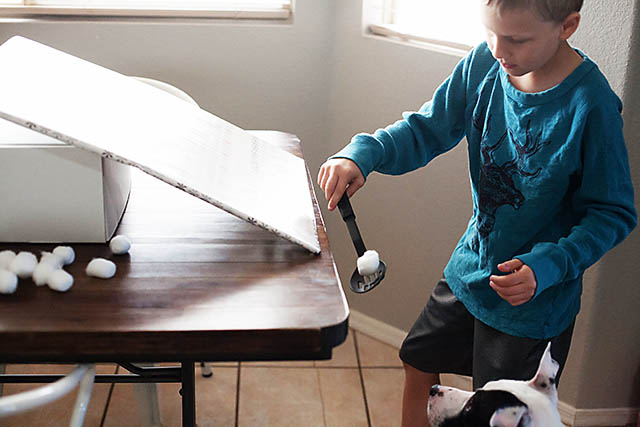 Snowball roll game using cotton balls from All for the Boys blog
