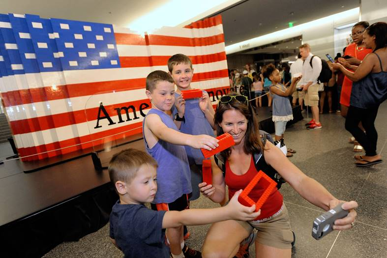 "The Colvin family, from left, Adrian, 4, Riley, 7, Jack, 10, and mother Shawna, of Tiffin, Iowa, take a ""selfie"" after helping build the world's largest LEGO American flag to celebrate the opening of the Innovation Wing at the National Museum of American History on Wednesday, July 1, 2015 in Washington. More than 15,000 museum visitors helped create the 9.5-by-14-foot flag using more than 100,000 LEGO bricks. (Steve Ruark/AP Images for LEGO)"