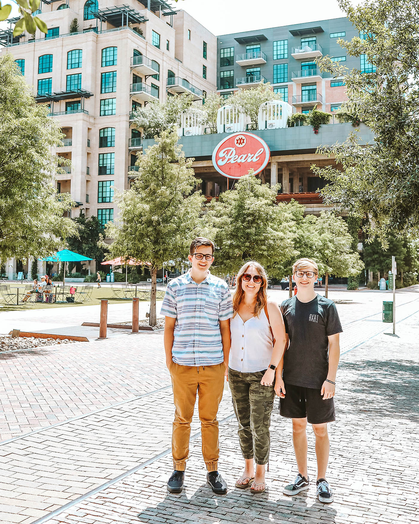 Mother and two teenaged sons standing in front of the Pearl District sign in San Antonio