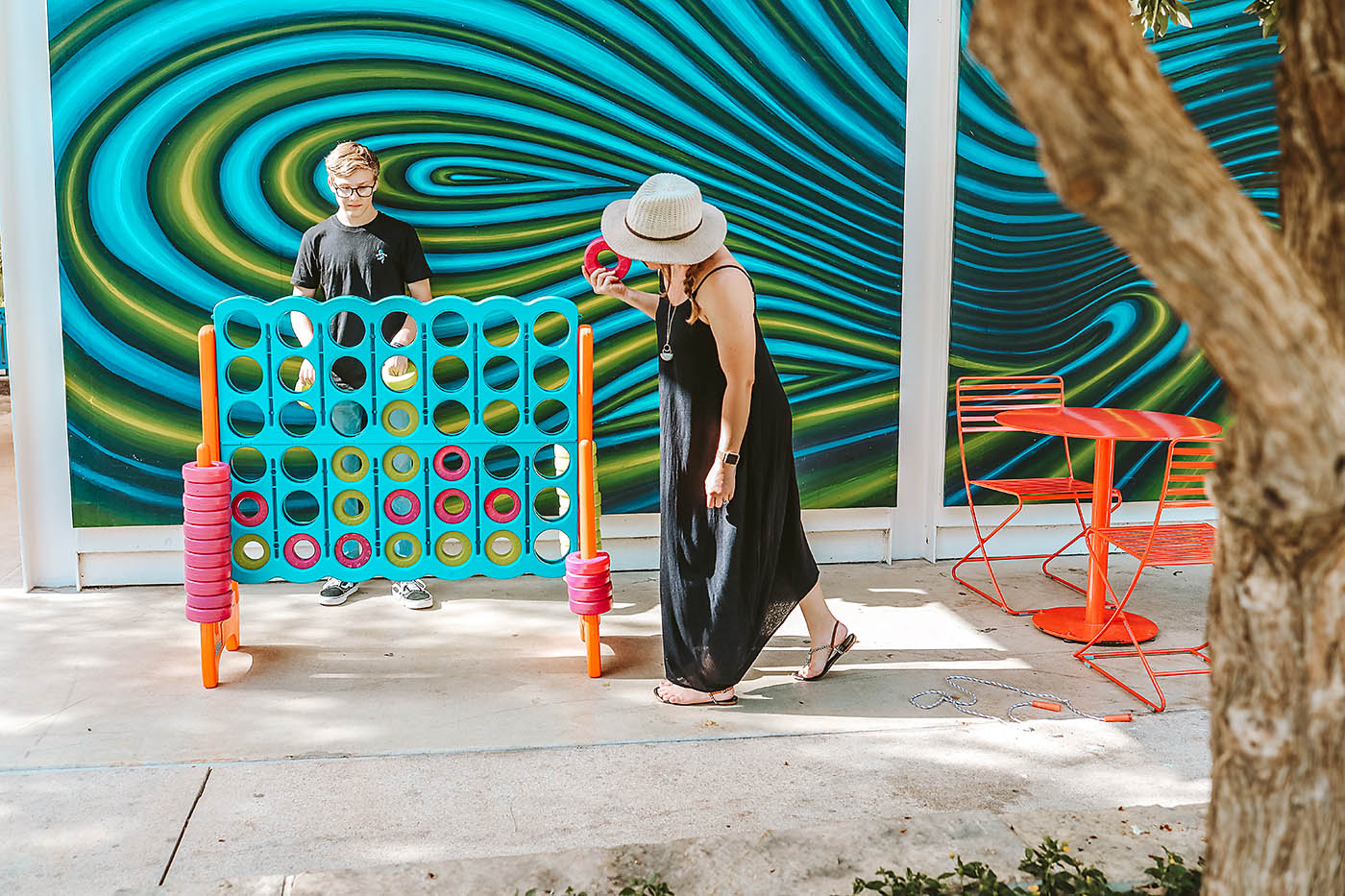 Woman and son playing large connect 4 game in front of blue and green wall at a park in San Antonio