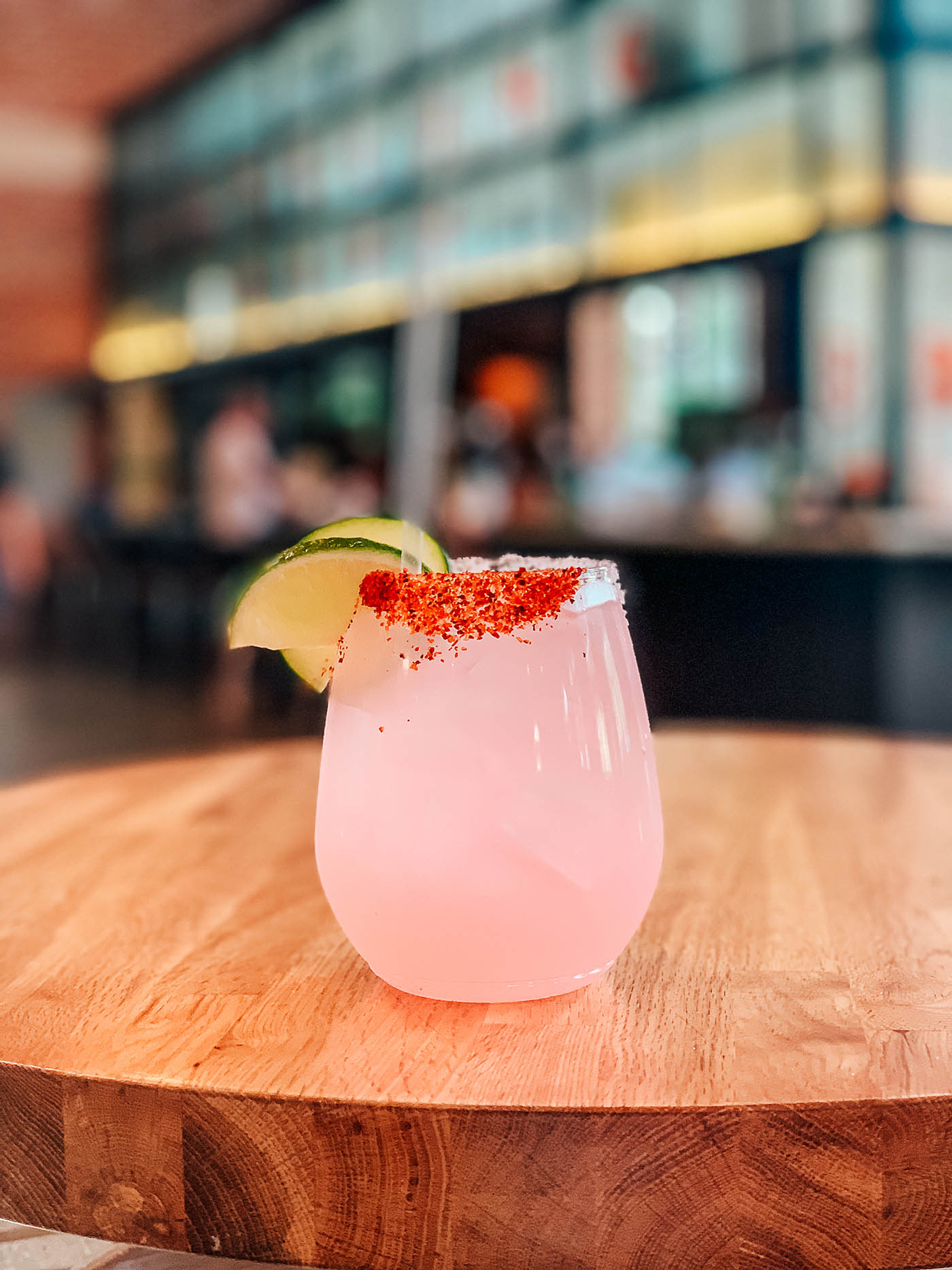 A pink cocktail with dark pink salted rim and lime