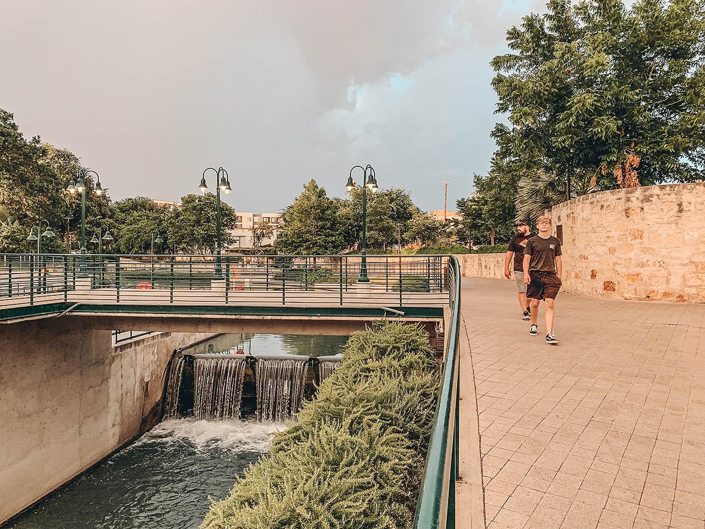Teenaged boy walking on the San Antonio Riverwalk with waterfall below