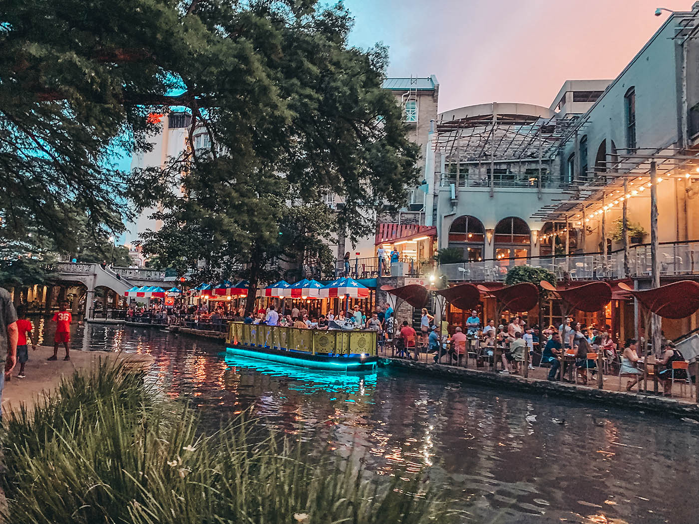 Small boat on San Antonio Riverwalk at sunset with lights