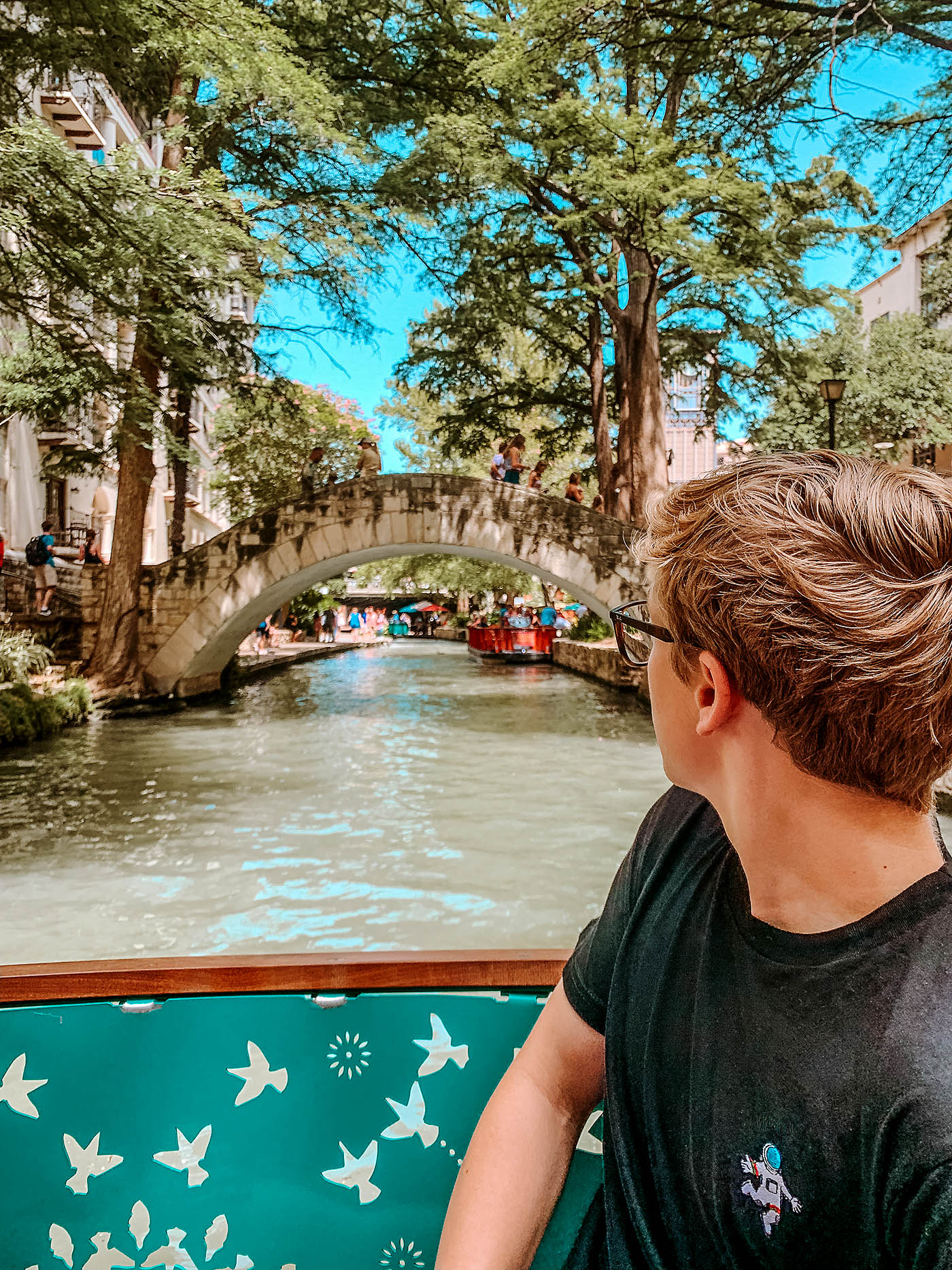 Teenaged boy looking over his shoulder at the River in San Antonio on a river cruise