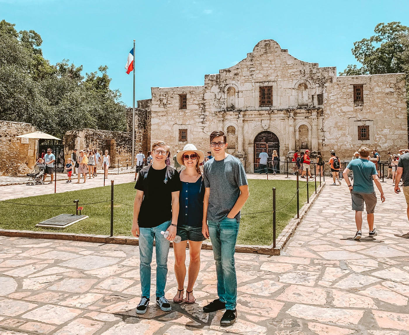 Mom and two teenaged sons in front of the Alamo in San Antonio