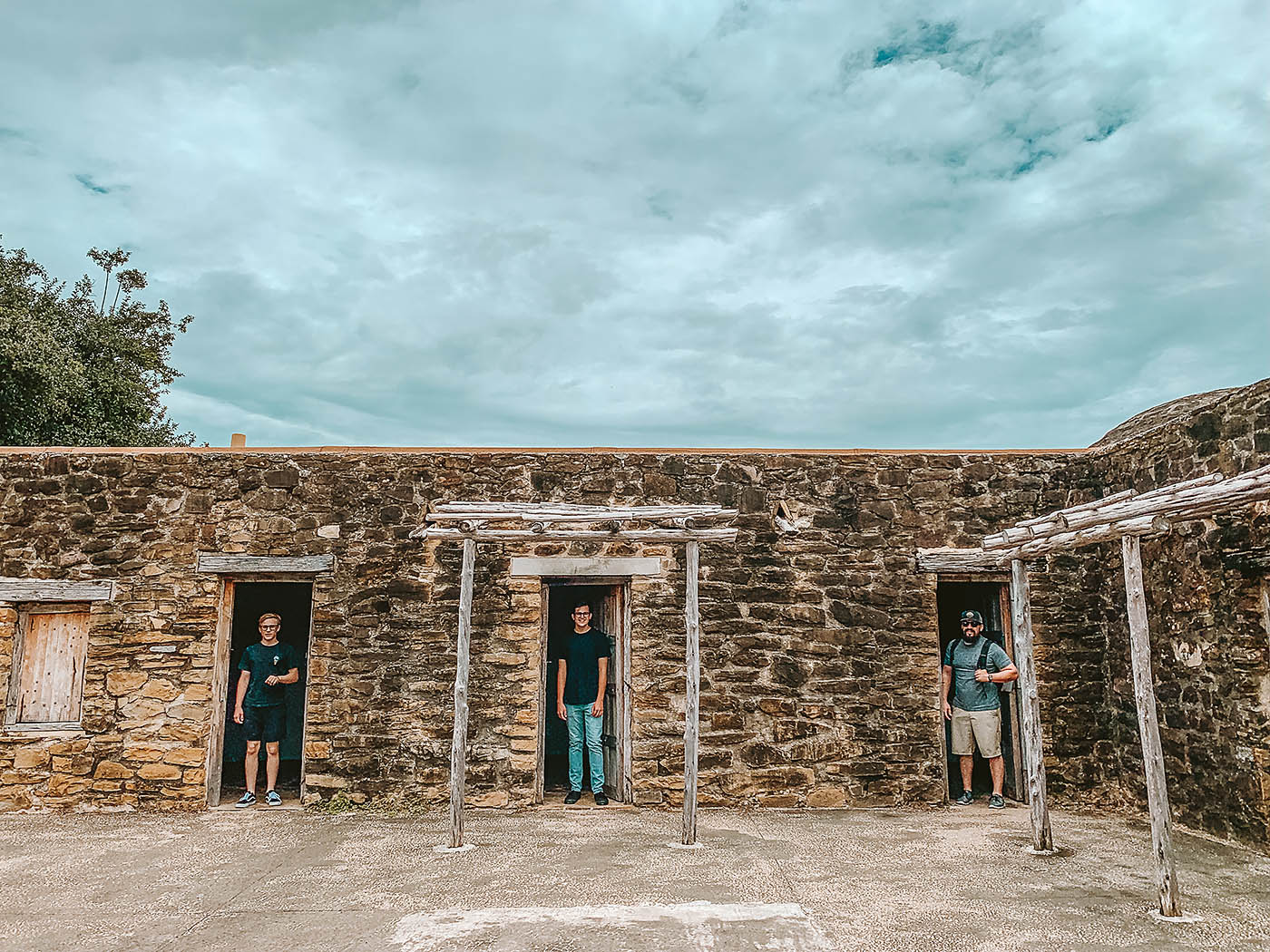 A father and two teenaged sons standing in doorways at a San Antonio mission