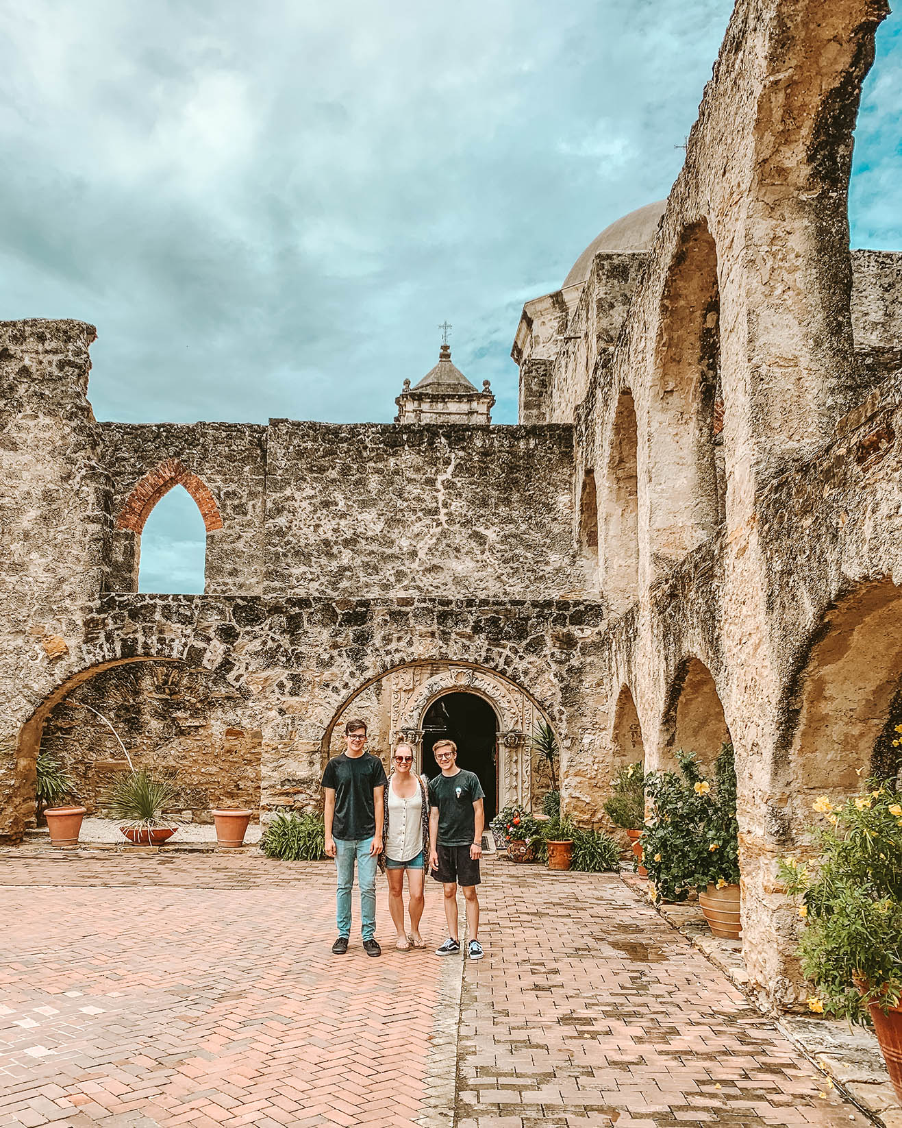Mother and two teenaged sons standing in central area of a San Antonio Mission